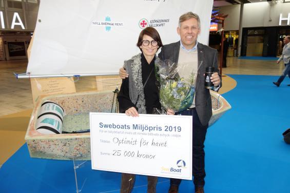 Branschorganisationen Sweboats miljöfond delande ut 25 000 kronor till projekt Optimist. Optimistjollen är byggd av plastskräp som samlats in från strandstädningar. Sharon Emanuel från Håll Sverige Rent och Thomas Hansson-Mild från Svenska seglarförbundet tog emot checken.