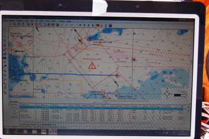 Bilden är från Ålands hav. Vår position är ungefär i mitten, i cirkel där det blå strecket slutar. Vi har just passerat det övre högra hörnet i ett trafiksepareringsområde. <br />Så får man inte göra, trafiksepareringsområden ska korsas vinkel-rätt. Vi ser också att ett fartyg är på väg att korsa vår kurslinje akter om oss. Snett upp till höger framför oss (grön triangel med röd fyrkant runt om) ser vi en båt som går i fel \