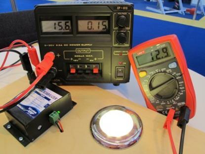 Transformatorn, mitten överst,ger här 15,6 volt till voltstabilisatorn, till vänster. Spänningen till LED-lampan är endast 12,9 volt. Voltstabilisatorn tar hand om 2,7 volt och skyddar därmed LED-lampan från skada.