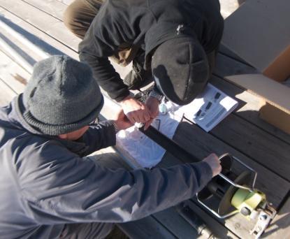 Vita duken på bryggan ligger som skydd. Små skruvar, som man lätt tapparnär fingrarna är kalla,ska monteras och de säkras med locktite.