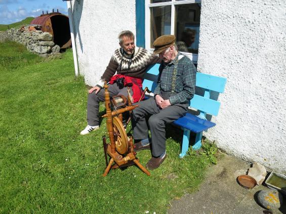 Lars Nyström, till vänster, får en lektion om hur man spinner garn av Stuart Tomson.