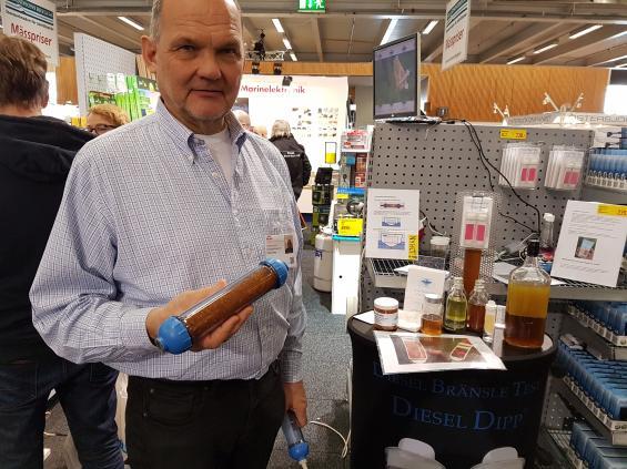 Stefan Berg från Dieseldipp visar behållaren innehållande kiselgel. Om behållaren monteras på avluftningsslagen för dieseltanken sägs kiselgelen hålla vattnet borta från tanken.