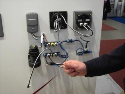 Raymarines nätverk Seatalk NG är inte NMEA 2000 certifierat, men det kommunicera med NMEA 2000. I handen håller säljaren en adapterkabel som används för att koppla ihop Raymarines Seatalk NG med andra märken viaNMEA 2000.
