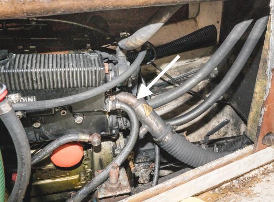 Vatten har runnit tillbaka ner i motorn så det korroderat vid värmeväxlaren. Från den läcker det vatten. Det har i sin gjort att reglage och motorfäste också har korroderat. Motorn har vid detta tillfälle inte undersökts invändigt men tredje cylindern saknar kompression, varför man kan anta att ventiler och ventilsäte har korroderat. Kolv och cylinder kan också vara påverkade.<br />Pilen pekar på avgaskröken.