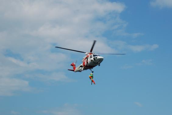 Räddningshelikopern vinscharombord ytbärgaren och en skadadperson. Bilden är från en övning vid Räfsnäs,Tjocköfjärden. Hur räddas en ryggskadad person från en liten segelbåt på ett hav där vågorna går höga?