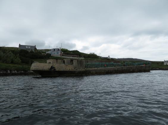 Detta fartyg i ferrocement lär ska ha legat här sedan kriget. Nu används det som kaj för fiskebåtar i en vik utanför Tarbert.
