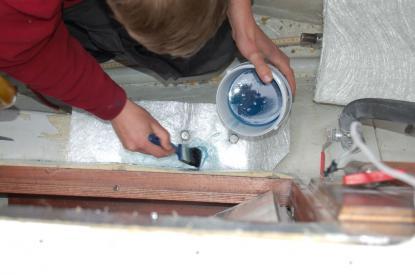 Glasfibermattor läggs runt det spacklade området. Innan plastning sker måste det tvättas med aceton och trasa. Detta för att plasten ska fästa på underlaget.