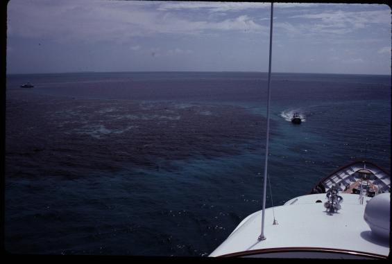 """Här har vi kört Mi Gaea, en 48 meters motorbåt, in i the Blue Hole utanför Belize kust 1992. Bortom """"hålet"""" syns området innanför revet med en kombination av sand och korallhuvuden som vi fick åka slalom emellan med hjälp av eye-ball navigation och en jolle med ekolod. Vi lyckades komma fram och lämna ringrevet utan missöden, men det var ingen avspänd resa."""